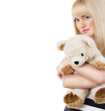 Pretty blonde girl wearing pajamas embraces teddy bear on white Royalty Free Stock Photo