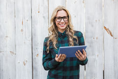Pretty blonde with glasses using tablet Stock Image