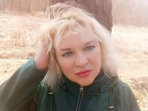 The blonde in green jacket with green eyes about tree of on the forest path in April. stock photo