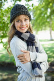 Pretty blonde in hat and scarf smiling at camera in the park Royalty Free Stock Photography