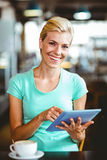 Pretty blonde having a coffee using tablet pc Royalty Free Stock Photos