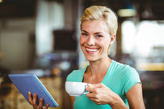 Pretty blonde having a coffee using tablet pc Stock Photography