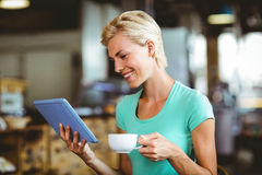 Pretty blonde having a coffee using tablet pc Stock Image