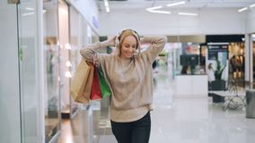 Pretty blonde is having fun in shopping mall listening to music through headphones, dancing with paper bags and looking stock video footage
