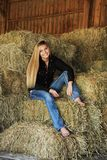 Pretty Blonde High School Senior Country Girl. Pretty, long blonde hair, blue eyes, High School Senior country girl portrait in a hayloft Royalty Free Stock Image