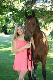 Pretty Blonde High School Senior Girl Outdoor with Horse. Pretty, long blonde hair, blue eyes, High School Senior girl outdoor portrait with Arabian Horse Royalty Free Stock Image