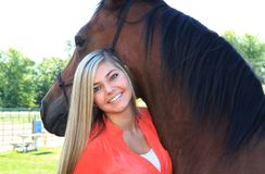 Pretty Blonde High School Senior Girl Outdoor with Horse. Pretty, long blonde hair, blue eyes, High School Senior girl outdoor equine portrait with Arabian Horse Stock Photography