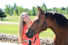 Pretty Blonde High School Senior Girl Outdoor with Horse. Pretty, long blonde hair, blue eyes, High School Senior girl outdoor equine portrait with Arabian Horse Stock Photos
