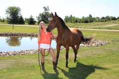Pretty Blonde High School Senior Girl Outdoor with Horse. Pretty, long blonde hair, blue eyes, High School Senior girl outdoor equine portrait with Arabian Horse Royalty Free Stock Photography