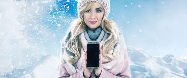 Pretty blonde holding a cellphone, winter bacgkround. Pretty blonde holding a mobile phone, winter bacgkround Royalty Free Stock Images