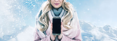 Pretty blonde holding a smartphone, winter weather. Pretty blond lady holding a smartphone, winter weather Royalty Free Stock Image