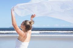 Pretty blonde holding up white shawl on the beach Royalty Free Stock Photos
