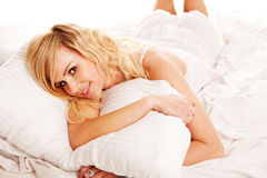 Pretty blonde hugging her pillow in the morning Royalty Free Stock Photos