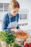 Pretty blonde in a kitchen. A young and beautiful woman in a blue shirt and apron is preparing a fresh vegetable salad at home in the kitchen royalty free stock photography