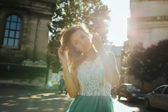 Pretty blonde model in lace dress posing in sun rays at the stre. Pretty blonde lady in lace dress posing in sun rays at the street Stock Image