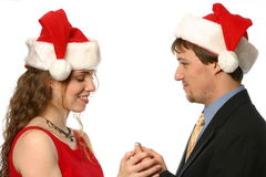 Pretty blonde lady smiling in santa hat getting ring from young man. Pretty blonde lady with blue eyes and dimples wearing a santa hat and smiling being offered Royalty Free Stock Photos