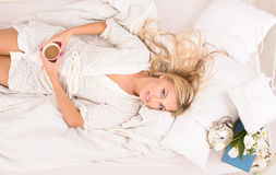 Pretty Blonde Lady With Cup Of Coffee In Bed Royalty Free Stock Photos
