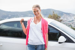 Pretty blonde leaning on the door and holding key Stock Photography