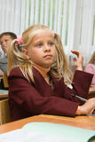 The pretty blonde at a lesson. Children at school at a lesson. The thoughtful girl sits at a school desk Stock Images