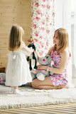Pretty blonde little girl and her mother play with soft toys Royalty Free Stock Photos