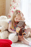 Pretty blonde little girl sits on carpet near window stock images