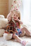 Pretty blonde little girl sits on carpet near window Royalty Free Stock Photography