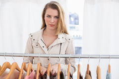 Pretty blonde looking at camera by clothes rail Stock Photo