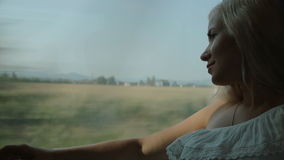 Pretty blonde looks through the window of the moving train. Pretty blonde looking through the window of the moving train stock footage