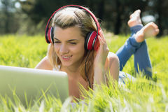Pretty blonde lying on grass using laptop listening to music Royalty Free Stock Photos