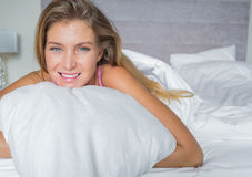 Pretty blonde lying in her bed smiling Royalty Free Stock Images
