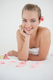 Pretty blonde lying on massage table with rose petals Stock Photography