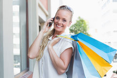 Pretty blonde making a call and holding shopping bags Royalty Free Stock Image
