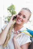 Pretty blonde making a call and holding shopping bags Royalty Free Stock Images