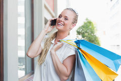 Pretty blonde making a call and holding shopping bags Stock Photos