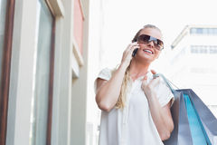 Pretty blonde making a call holding shopping bags Stock Photos