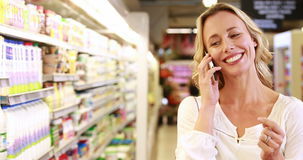 Pretty blonde making a phone call while shopping stock video footage