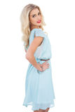Pretty blonde model in blue dress posing hand on the hip Stock Images