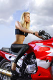 Pretty blonde on a motorcycle. Pretty blonde woman on a big red motorcycle stock images