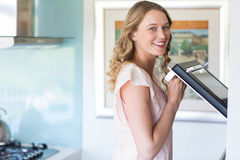 Pretty blonde opening the oven Royalty Free Stock Photography