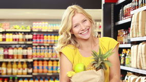Pretty blonde with paper bag doing thumbs up. In grocery store stock video