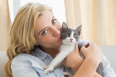 Pretty blonde with pet kitten on sofa Stock Photography