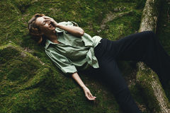 Pretty blonde posing on moss dressed in masculine shirt and stylish trousers. Royalty Free Stock Photos