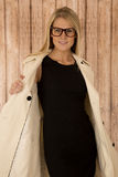 Pretty blonde posing with open coat and wearing glasses Stock Photo