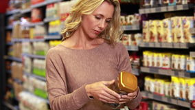 Pretty blonde putting product in trolley. In grocery store stock footage