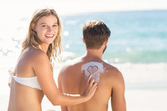 Pretty blonde putting sun tan lotion on her boyfriend Royalty Free Stock Images