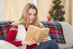 Pretty blonde reading book at christmas time Royalty Free Stock Photography