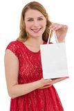 Pretty blonde in red dress holding a shopping bag Royalty Free Stock Photography