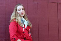 Pretty blonde in red jacket against red barn wall Royalty Free Stock Images