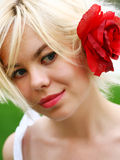 Pretty blonde with rose in hairs Royalty Free Stock Images
