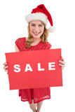 Pretty blonde in santa hat holding a red sale poster Royalty Free Stock Photo